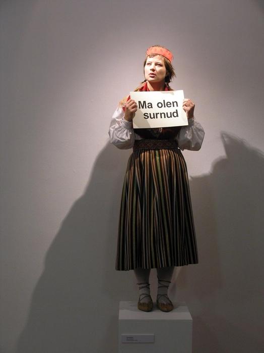 Flo Kasearu, Estonian Sculpture (I am dead)—Performance réalisée au Tallinn Arthall, Estonie, au Warszawski Aktyw Artystow, Varsovie, Pologne et devant l'ambassade estonienne de Berlin, Allemagne